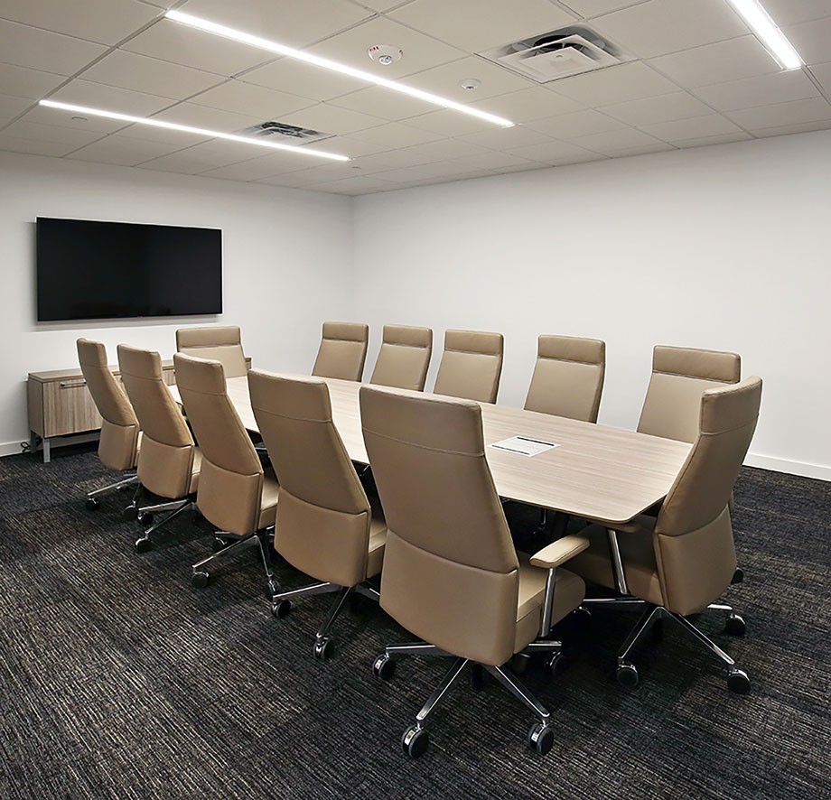 Conference room with 12-person round table and wall-mounted TV